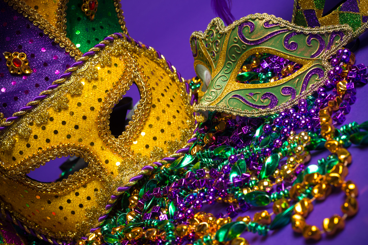 Festive Grouping of mardi gras, venetian or carnivale masks on a purple background