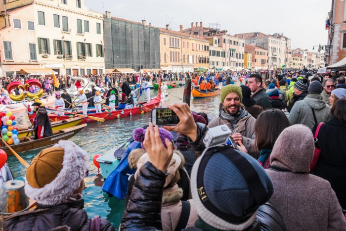 Venice, Italy - January 24, 2016: Crowds enjoy, cheer and take photographs the Venetian Festival on the Water in Cannaregio as part of the 2016 Venice Carnival celebrations.