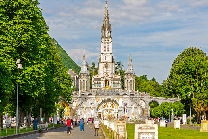 Lourdes, France - June 06 2012: The front facade of The Basilica of our Lady of the Rosary. Lourdes is a major place of Roman Catholic pilgrimage and of miraculous healing. It was designed by architect Leopold Hardy, completed in 1899, consecrated in 1901