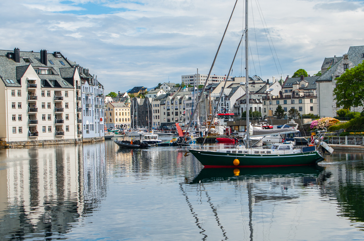 Boats for sailing, fishing and touring gather in the port of Alesund, Norway.