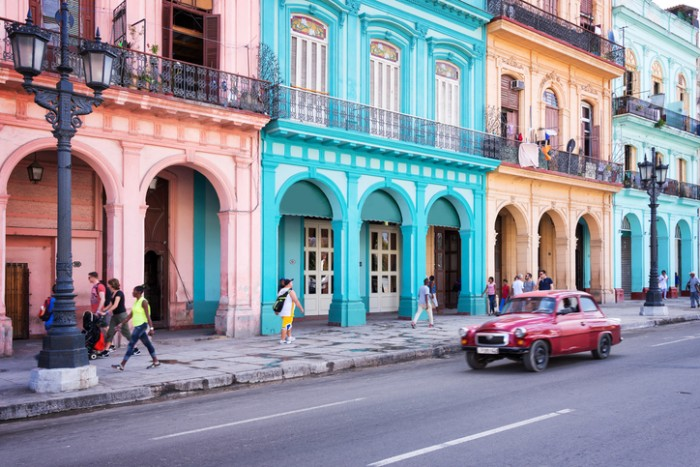 Havana, Cuba - April 18, 2016: Classic vintage car and colorful colonial buildings in the main street of Old Havana