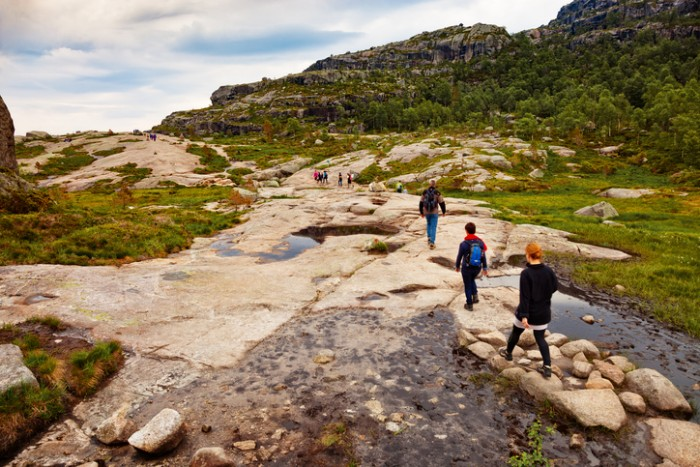 Forsand, Norway - July 12, 2015: Unidentified group of tourists on hiking trail to Preikestolen (Pulpit Rock).
