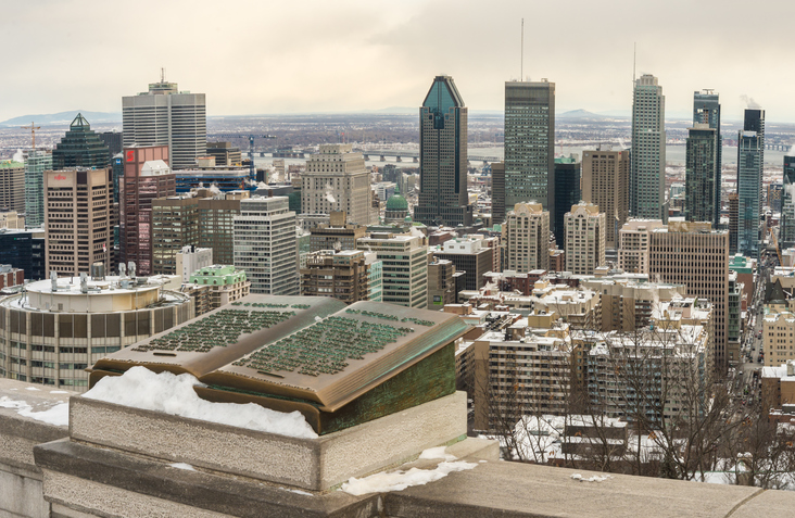 Montreal, Canada - December 15, 2016: Montreal Skyline in winter and Commemorative Jacques Cartier plaque located on the balustrade of the Kondiaronk lookout on Mount Royal