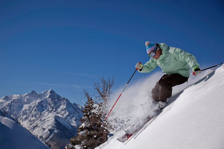 Young hot skier in powder with blue skies in front of beautiful mountains
