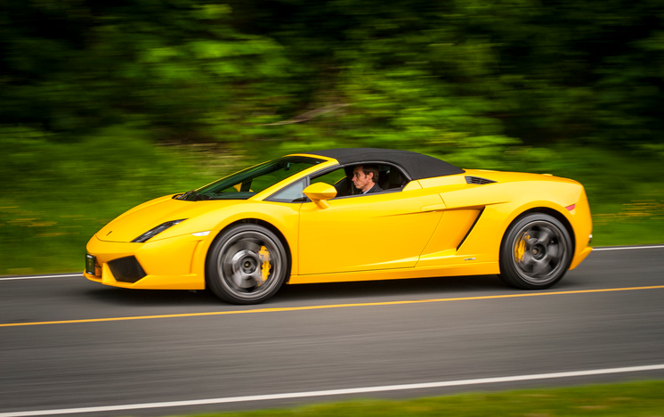 "Vancouver, Canada - June 8, 2013: A yellow Lamborghini Gallardo is seen being driven on the road by a young male driver, during a local ""Cars and Coffee"" event."
