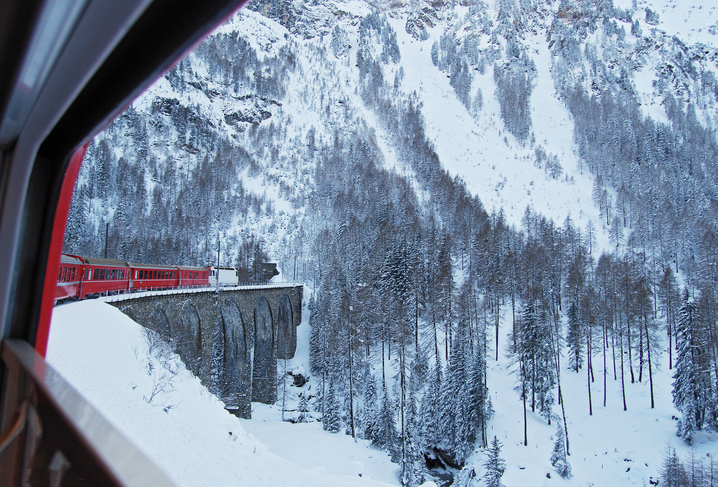 The Rhaetian Railway Express train from Chur to St. Moritz  on one of the many viaducts of the Albula line under cold winter conditions.