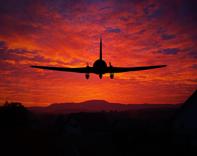 Sunset with a plane silhouette, flying above the houses.