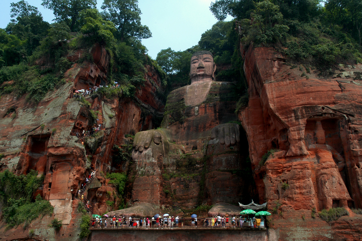 This statue of Buddha is 71 meters high and located near Leshan in the province Sichuan (western part of China). It's carved out of a cliff, overlooking the confluence of the rivers Min and Dadu. Work took place between 713 and 800 AC. From the top you can walk down to the feet and up agian to monastery and temples. MI#1723A.