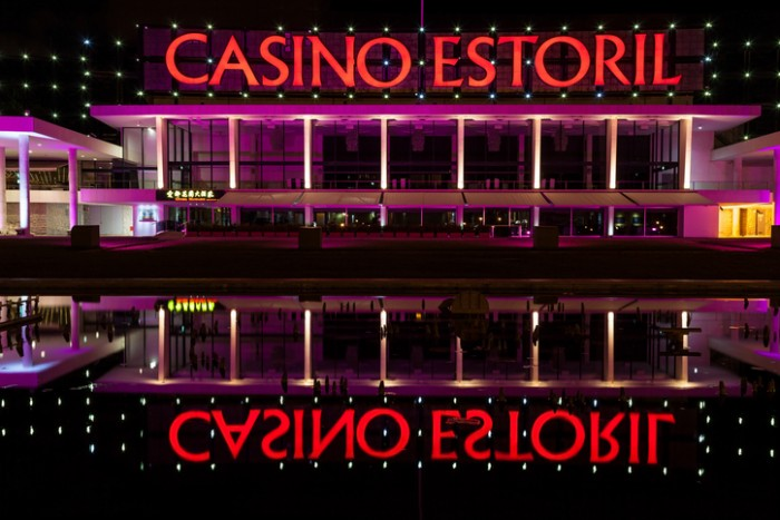Estoril, Portugal - July 4, 2012: Facade of Estoril Casino illuminated at night and reflected in a pond