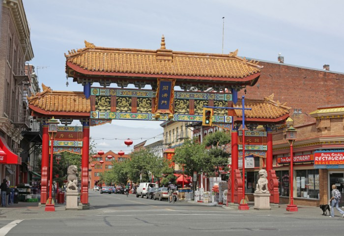 """Victoria, Canada - June 15, 2012: Victoria's Chinatown National Historic Site of Canada. The Gate of Harmonious Interest welcomes pedestrians and motorists on Fisgard Street. Spring morning."""