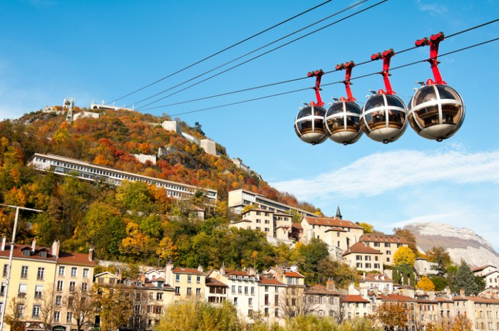 Grenoble, France - November 1, 2011: Cable car connecting the city of Grenoble to the Bastille on top of the mountain. Passengers inside the cabins and autumn colours on the mountain.
