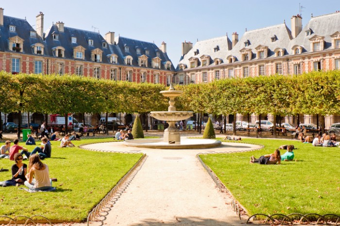 Paris, France - September 24, 2013: People relaxing on green lawns of the famous Place des Vosges - the oldest planned square in Paris.