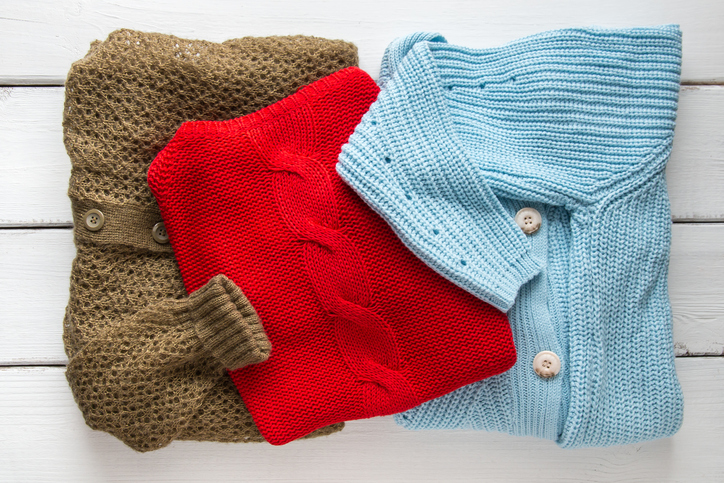 Stack of women's knitted sweaters and cardigans.