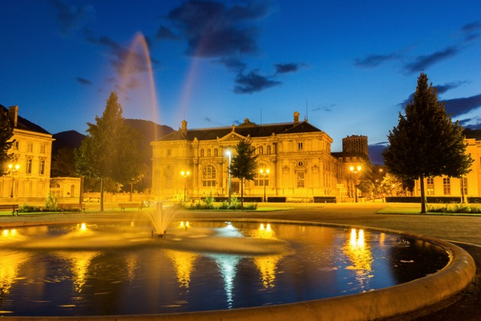 Grenoble, Rhône-Alpes, France - August 19, 2015: Place de Verdun with Grenoble-Library Museum in Grenoble in France. There is a fountain in the foreground and there are no people in the photo.
