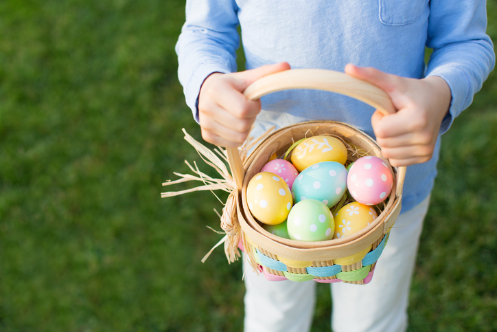 easter and spring concept, boy holding basket full of colorful eggs standing on the grass
