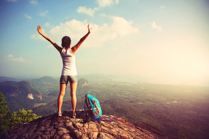woman hiker enjoy the view at landscape on mountain peak cliff