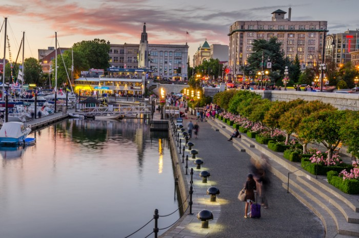 Victoria, BC, Canada - July 4, 2014: Inner Harbour pathway crowded with people at sunset. This patch of waterfront is the location of many tourist attractions and recreational activities.