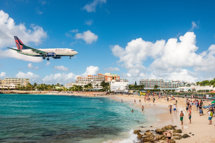 Philipsburg, Sint Maarten- December 30, 2013: A jet approaches Princess Juliana Airport above onlookers on Maho Beach. The short runway gives beach goers close proximity views of the planes.