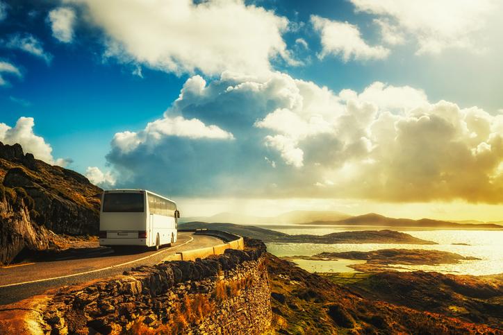 Tourist white bus on mountain road. Ring of Kerry, Ireland. Travel destination