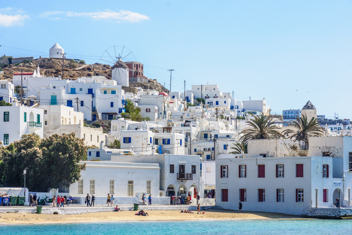 Mykonos, Greece - October 2, 2011: Village and beach scene, with local businesses, windmills, locals and visitors, in Mykonos, Mykonos Island, Greece