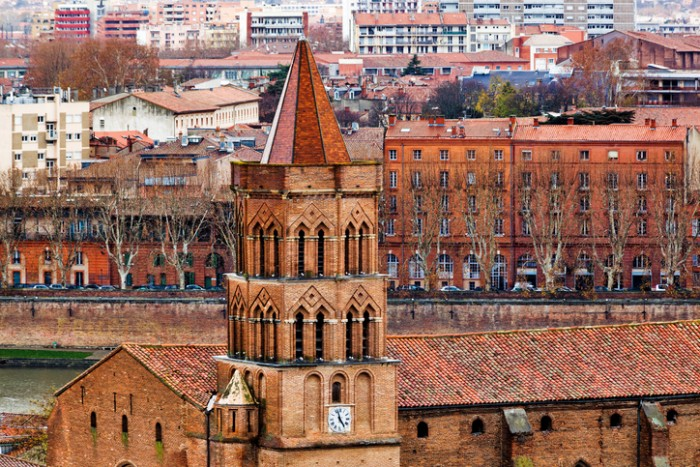 Saint Nicolas V-th century church on Toulouse city center and Garonne river background, France