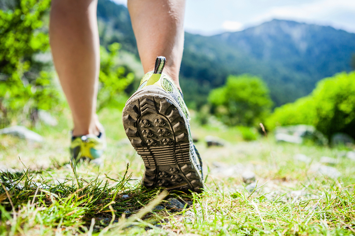 Woman hiking in mountains, adventure and exercising. Fitness in sunny  summer nature outdoors. Legs and sport shoes walking on grass.