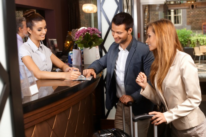 Receptionist giving tourist information to hotel guests upon arrival..