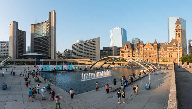 Toronto, Canada - September 6, 2015: Panorama view of Nathan Phillips Square in Toronto bustling with locals and tourists on a clear sunny afternoon, with the Toronto sign and the new and old City Halls in the background.