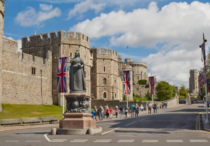 Windsor, United Kingdom - August 28, 2012: View of Windsor Castle, which is official residence of royal British family in Berkshire with Queen Victoria Statue on the foreground and the flow of tourists