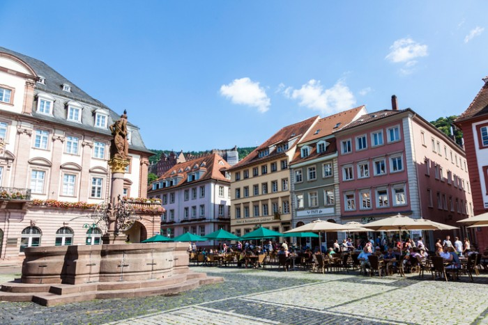 Freiburg, Germany - July 7, 2013: people visit Herkules fountain in Freiburg, Germany. The fountain at the central market place was build in 1709.