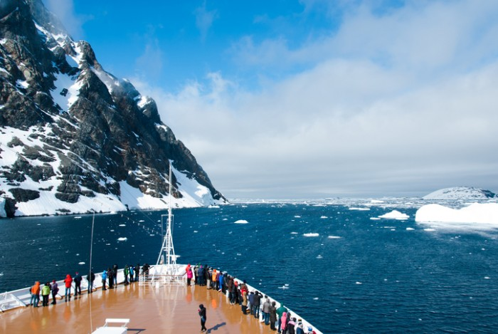 Cruise ship in Antarctica in sunny day passing the mountains and glaciers