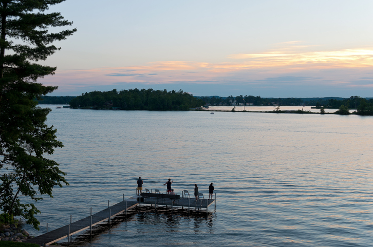 Baxter, MN, USA – July 3, 2016: Fishermen casting into water from pier at sunset in Steamboat Bay of East Gull Lake.