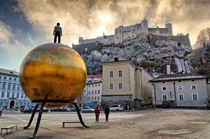 SALZBURG, AUSTRIA - DECEMBER 22: The Kapitelplatz with Stephan Balkenhol's 'Man on the golden Sphere' (German: Kugel mit männlicher Figur) and the Fortification of Salzburg (German: Festung Hohenslazburg) (HDR image) in Salzburg, Austria.