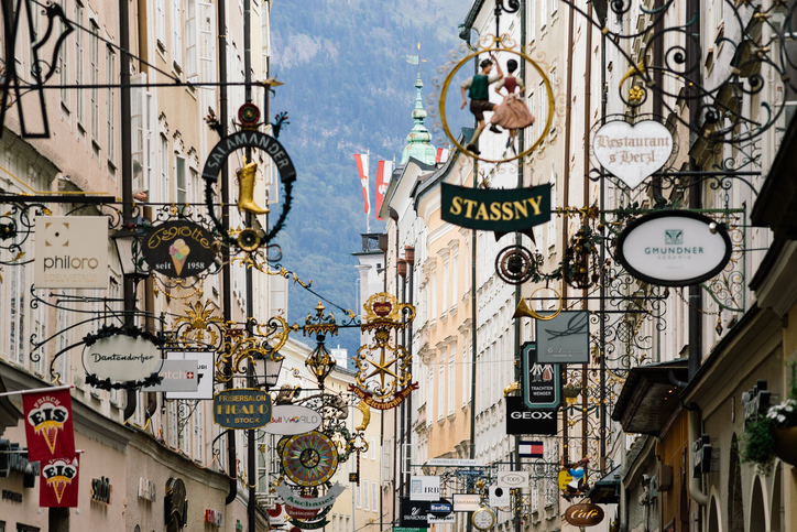 Salzburg, Austria - August 21, 2016: Famous historical street Getreidegasse with multiple advertising signs. Salzburg old town was listed as a UNESCO World Heritage Site in 1997.