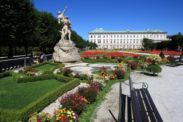 Salzburg, Austria - August 6, 2008: People visit Mirabell Gardens and Palace, famous landmarks of Salzburg and part of its UNESCO World Heritage Site. The palace was built in 1606.