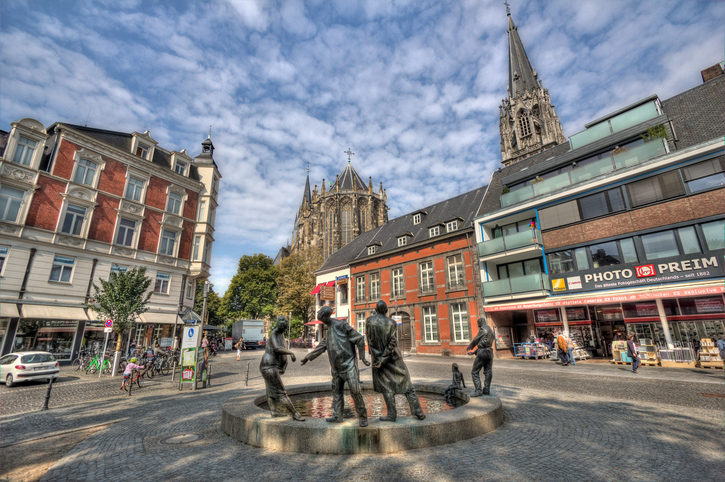 Aachen, Germany - August 28, 2013: Small square in the centre of Aachen with people shopping, a fountain and sculptures by sculptor Karl-Henning Seemann symbolizing money circulation and the towers of the cathedral in the background in Aachen, Germany on August 28, 2013