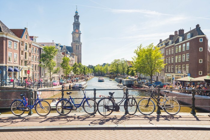 A view over one of the many canals in Amsterdam. Bicycles, canals, boats and the Westerkerk in the back, making this photo completely and typical Amsterdam.