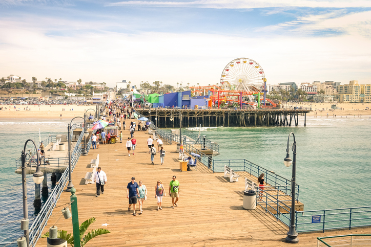 Santa Monica, CA, USA - March 18, 2015: high angle view of international tourists and local people at Santa Monica Pier with ferris wheel of Pacific Amusement Park - Famous american landmark on californian coast