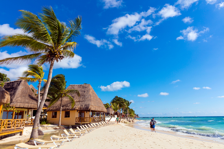 Playa del Carmen, Mexico - January 7, 2016: Unidentified people walking in white sand on the north beach of Playa del Carmen in Mexico.