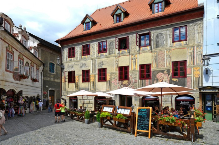 Krumlov, Czech Republic - August 11, 2013: Unidentified tourists, restaurant and house with sgraffito decorated facade in the Unesco World Heritage site in Bohemia