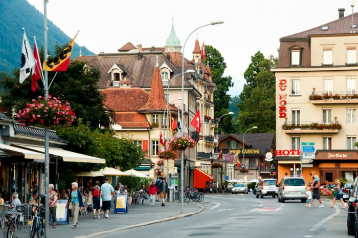 Interlaken, Switzerland - August 9, 2012: Commercial buildings & pedestrians on Hoheweg main street