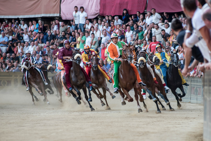 """Siena, Italy - August 16, 2015: Riders compete in the famous horse race """"Palio di Siena"""", Siena, Italy."""