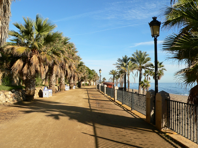 Scenic view of Marbella pedestrian way with palms, three tiled ornamental benches, the beach and the Mediterranean Ocean in a beautiful and sunny day