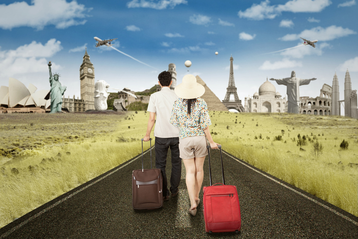 Couple walking on the road while carrying luggage to trip the famous landmarks