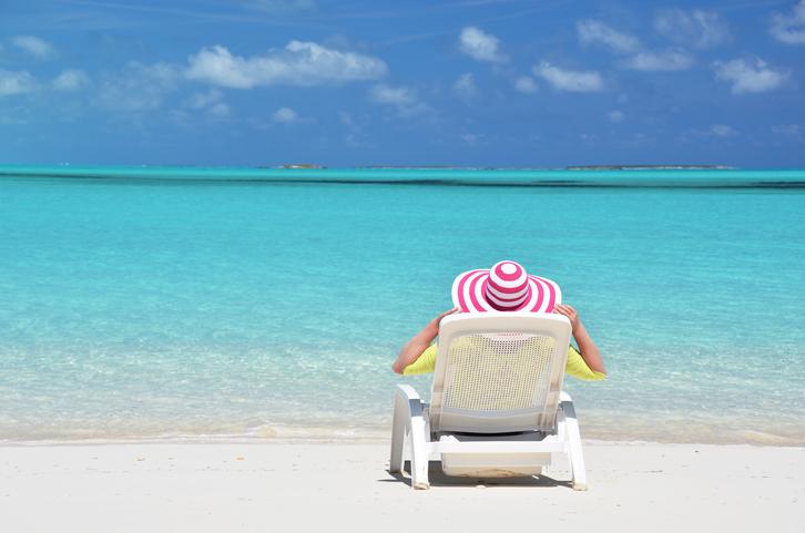 Girl in a striped hat on the beach of Exuma, BahamasExuma, Bahamas