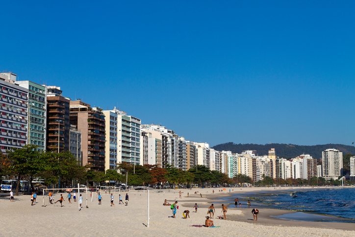 Niteroi, RJ, Brazil - August 16, 2011: Sunbathers relax at Icarai Beach in a beautiful day. Boys are playing soccer (left).