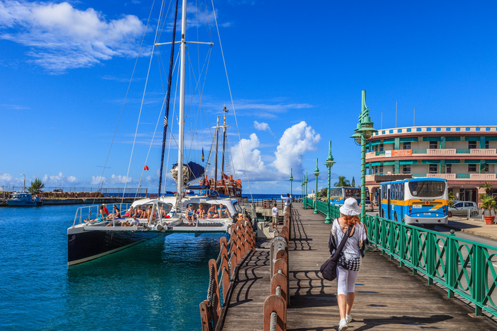 Bridgetown, Barbados - November 20, 2011: a catamaran with tourists on board is waiting to weigh anchor for a traditional excursion by sea. People are walking on the wharf located in the city downtown.