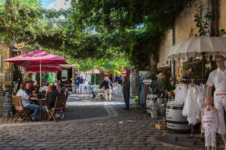 Saint Emilion, France – August 31, 2012: St. Emilion square with cafes and shops for tourists. Tourists rest at the tables of street cafe