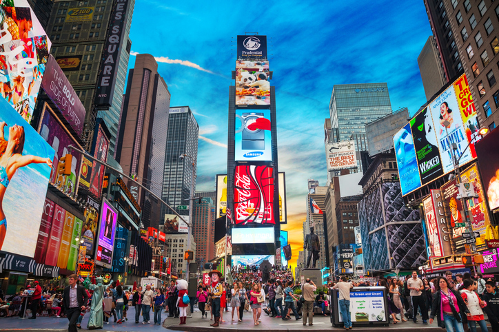 """New York, USA - May 11, 2013: Times Square with tourists. Iconified as """"The Crossroads of the World"""" it's the brightly illuminated hub of the Broadway Theater District."""