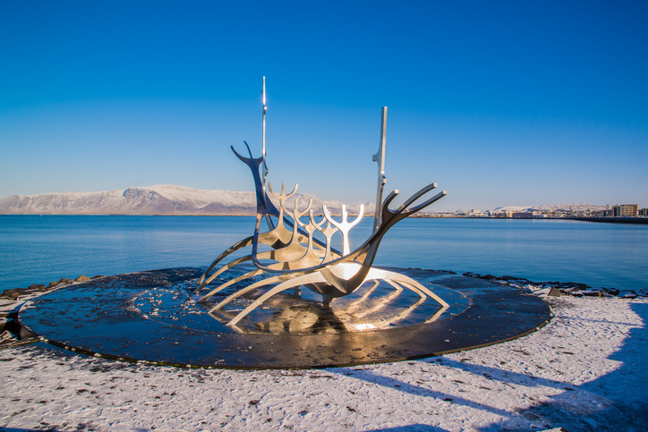 REYKJAVIK, ICELAND - CIRCA MARCH 2013 - Sculpture of Sun Voyager (Solfar) in Reykjavik, Iceland designed by Jon Gunnar Arnason, at the clear spring evening with sea and mountains in background;